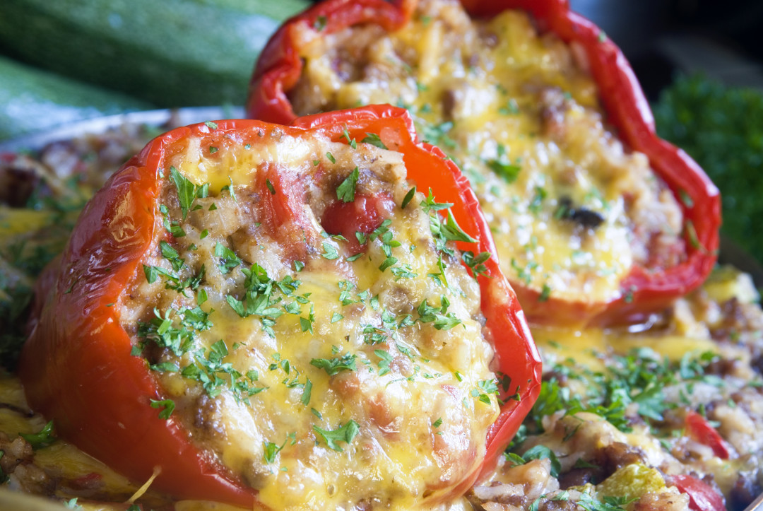 Red bell peppers stuffed with rice, tomatoes, and cheese; shot in natural light.