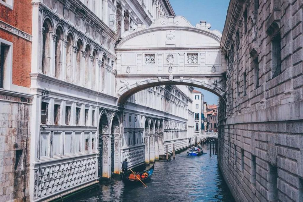 gondolas paddle along a canal in venice with an arch