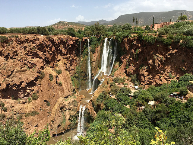 A view of the Ouzoud Falls water cascading through brick red slopes