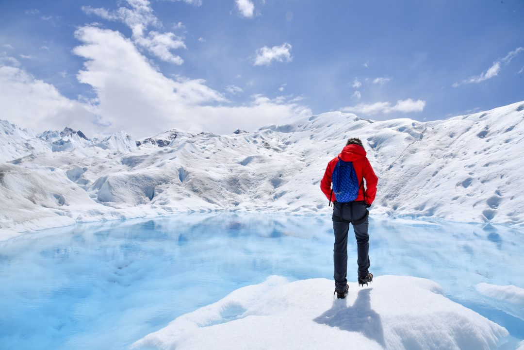 person in red coat standing on an iceberg
