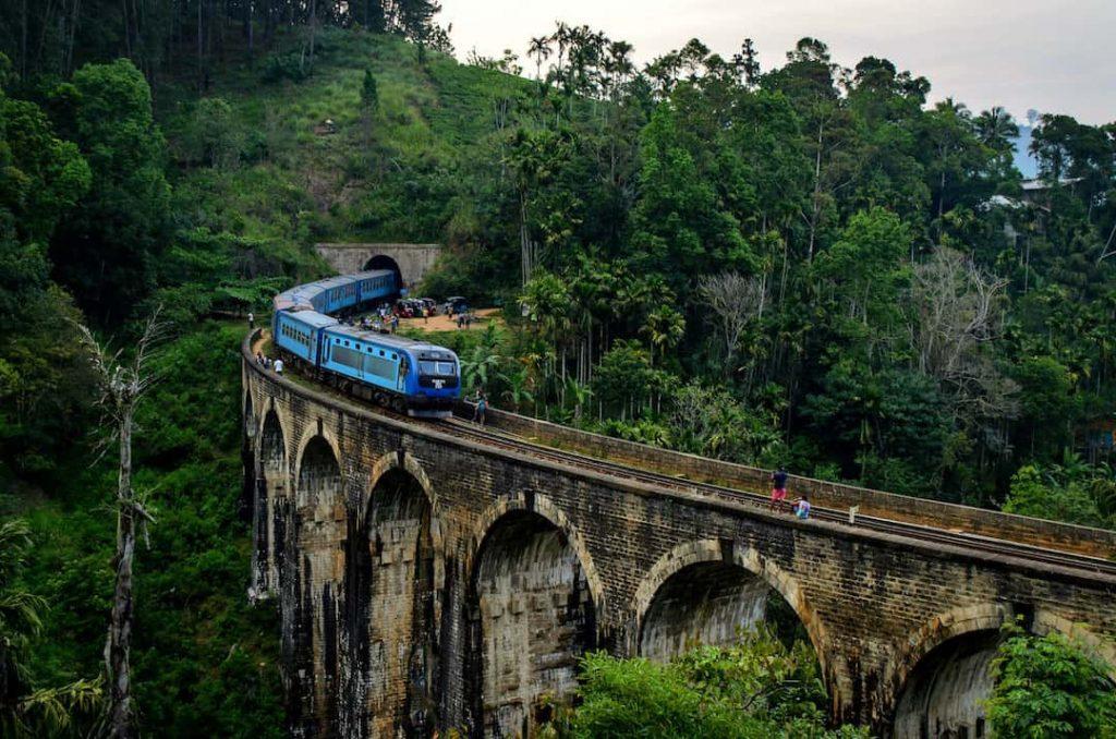 A blue train steams along Nine Arch Bridge in Sri Lanka
