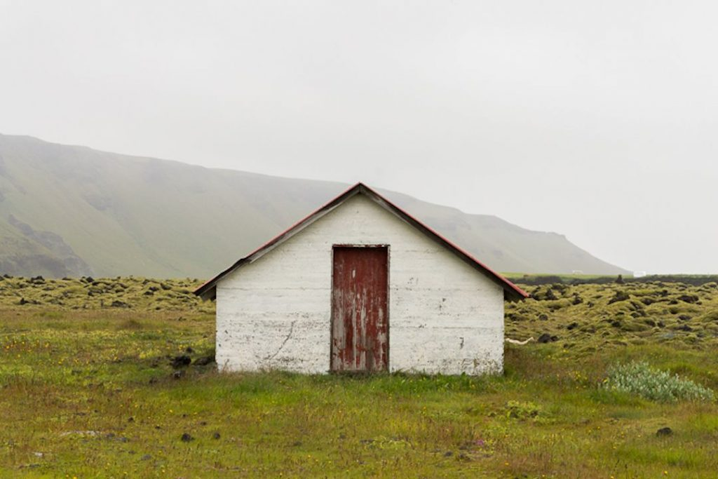 small white shack with a rusting red door in a green pasture