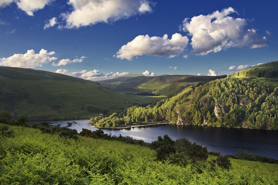 a blue lake between rolling hills and green pastures
