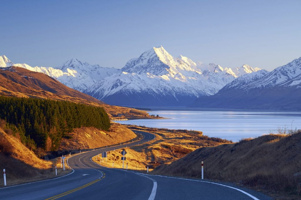 a highway snakes through new zealand's country side alongside a valley with a lake and mountains