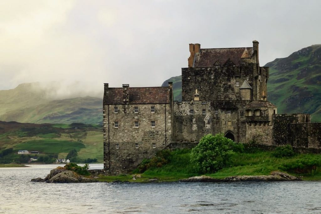 An old Scottish castle in the green countryside alongside a waterbody