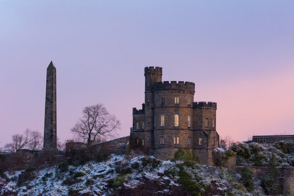 A Scottish castle with cylinder stone towers at dusk with patches of snow around it