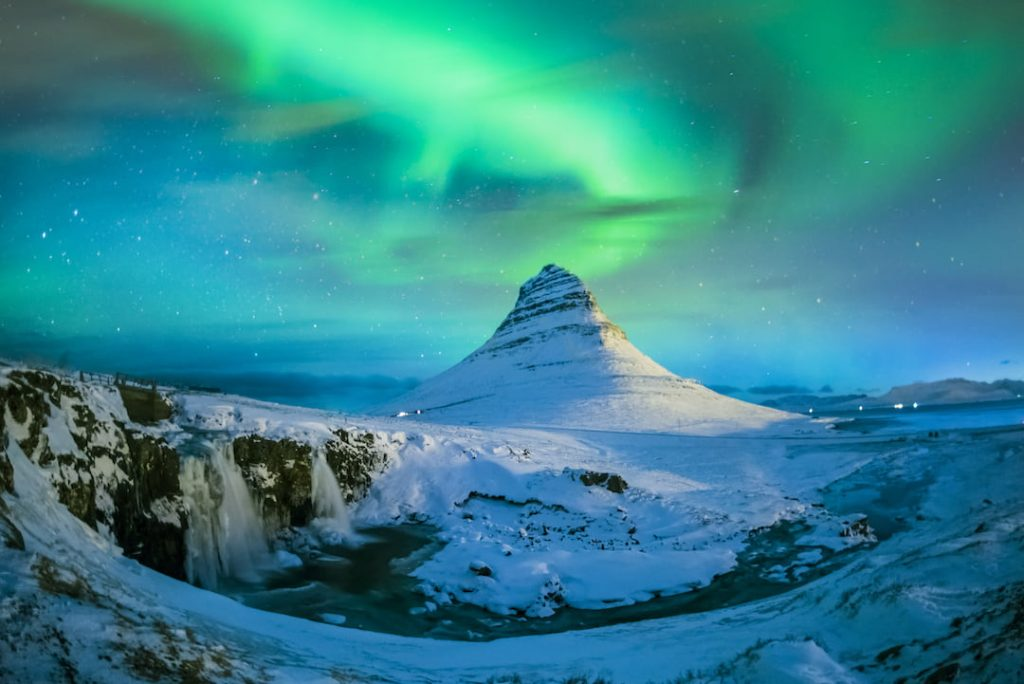 northern light blazing over a peak in Iceland