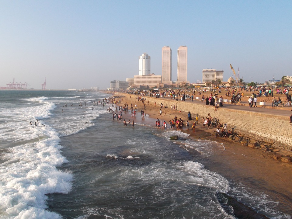 Colombo's city coastline with waves lapping up on the beach and the city scape in the background