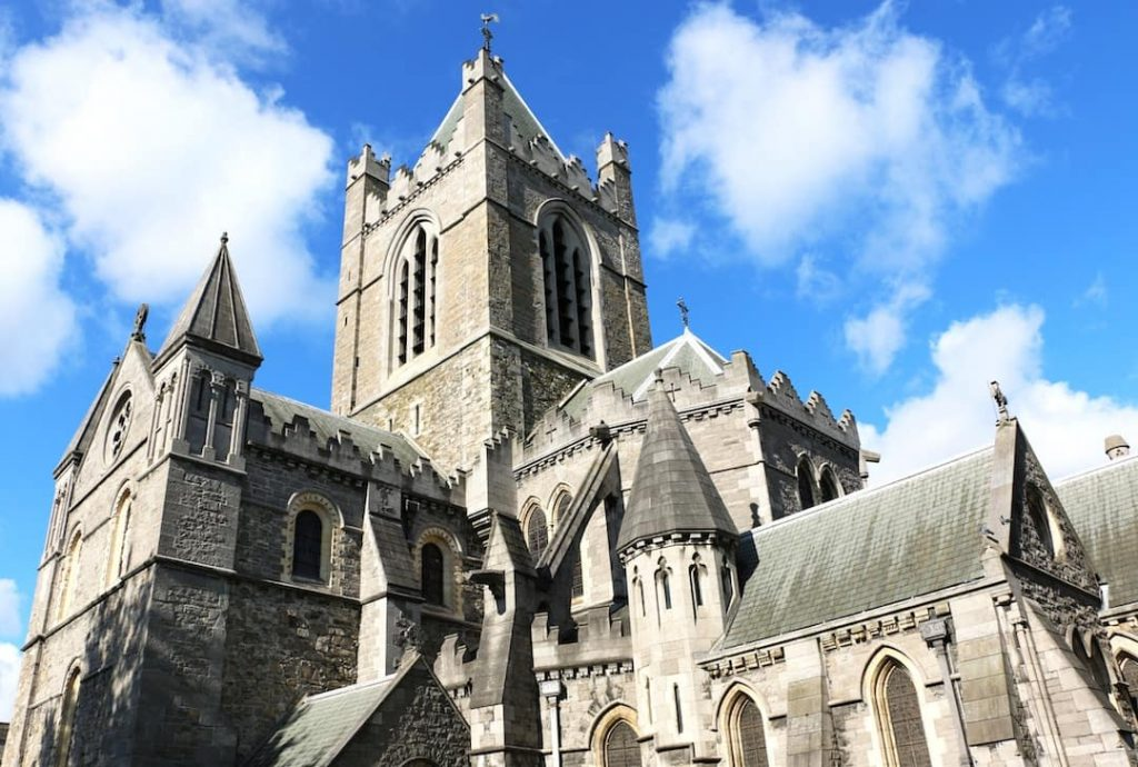 A great stone cathedral against the clouds and blue sky