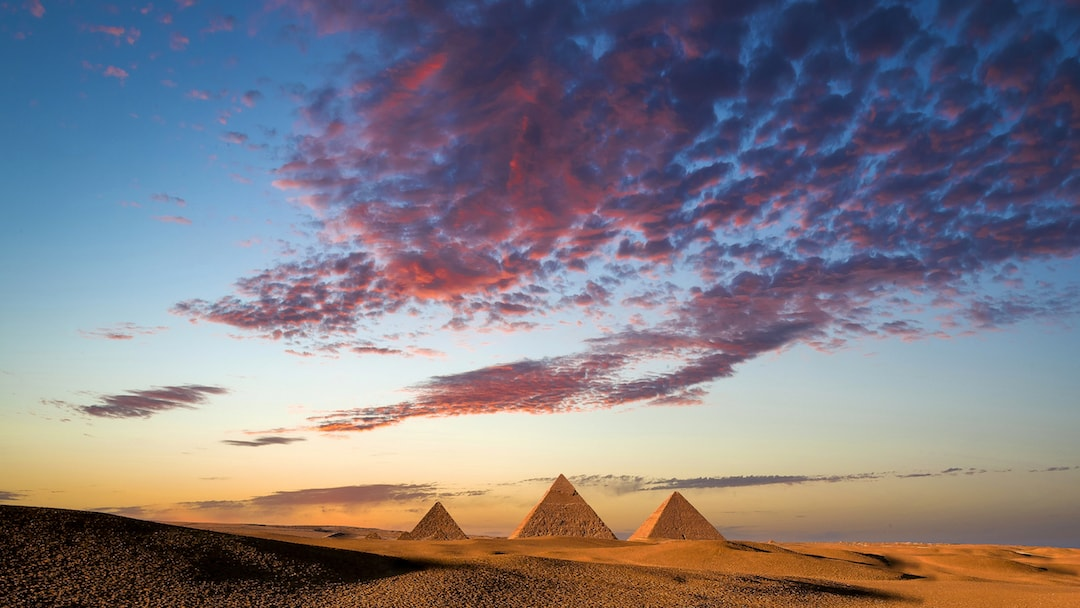Reddish pink clouds loom over Egypt's ancient pyramids of giza