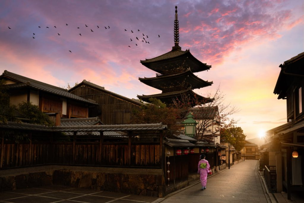 Traditional architecture in Japan, the sun has set, the sky is pink and birds fly across a cloud as a women walks through a pathway