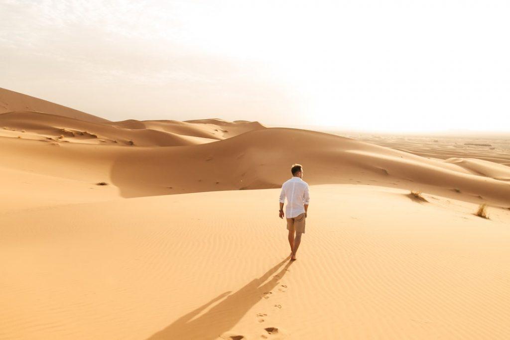man walking in a the Sahara desert