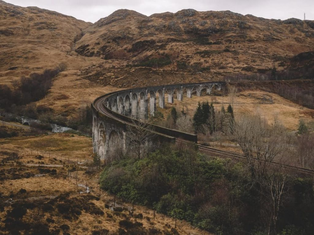 Ireland Vs Scotland: a stone train track with arches winds through scottish countryside