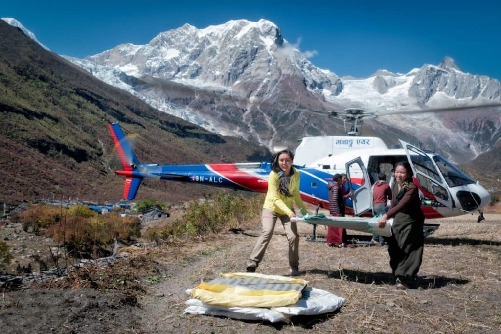 two woman unload relief supplies from a helicopter on Everest