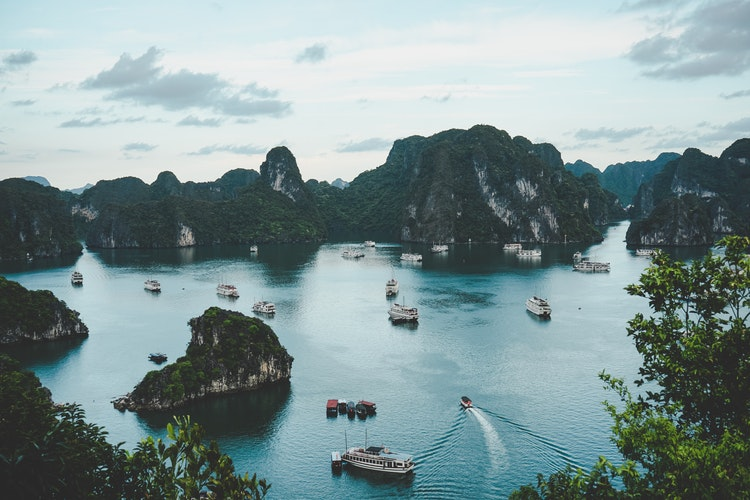Aerial view of Ha Long Bay with junk boats sailing through the limestone pillars