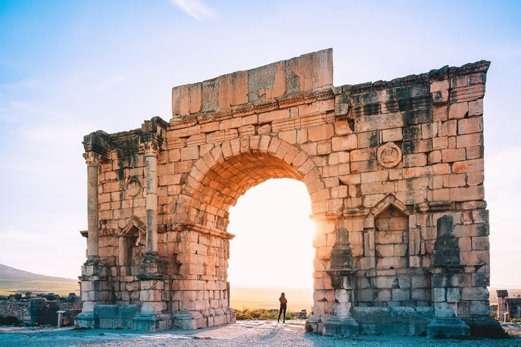 Sun peaks through a stunning arch in Volubilis of Morocco
