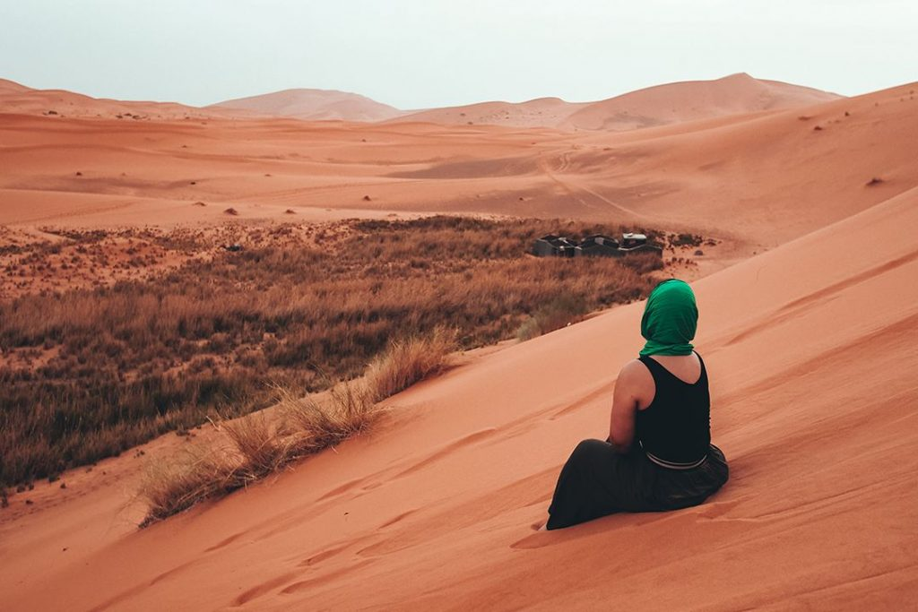 A traveller gazes out at the unending sandy landscape of Sahara Camp