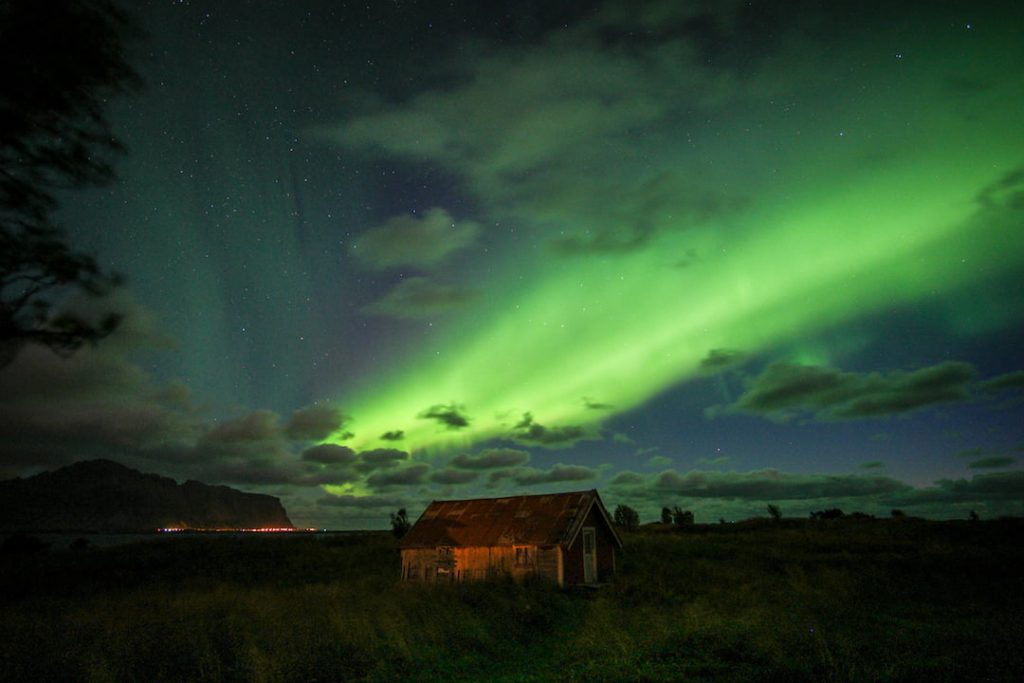 Aurora Borealis light up the skies above a cabin in Vestersand, Nordland, Norway, one of the best winter 2018 European destinations.