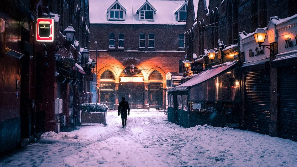 A man walks through a snowy Dublin street, with cosy lighting and pubs