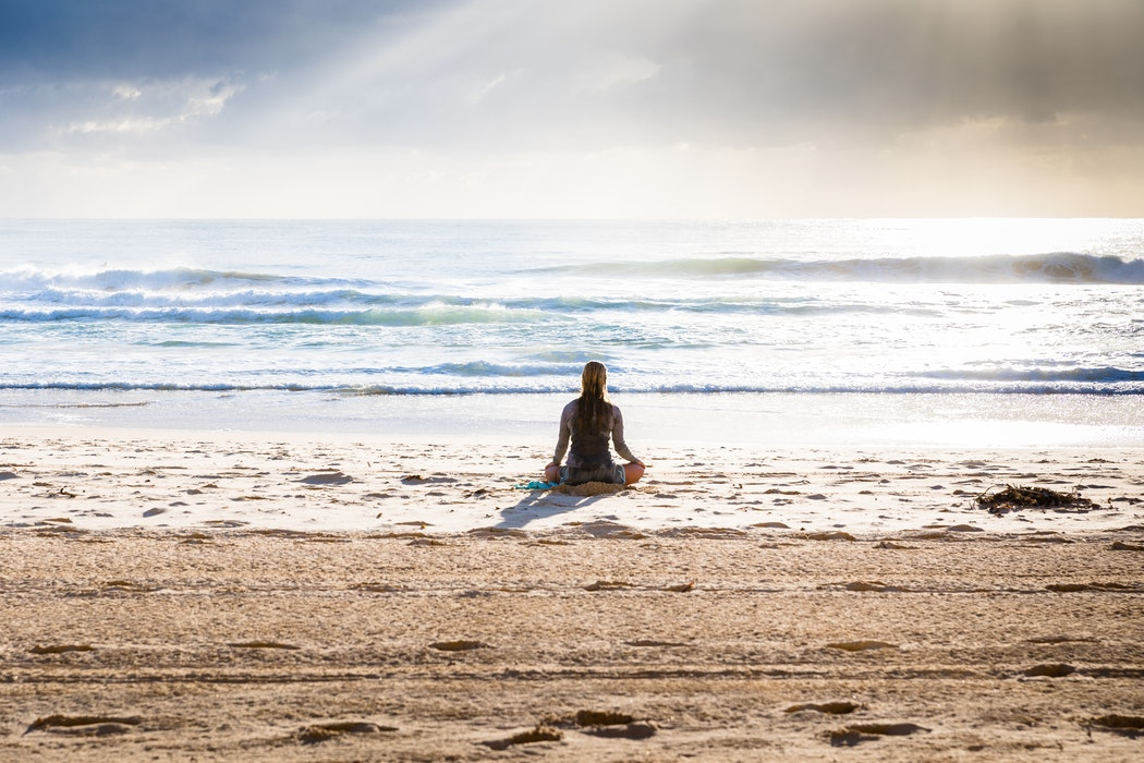 Are yoga retreats life changing: A woman sits in the shallows of a beach looking out in the horizon