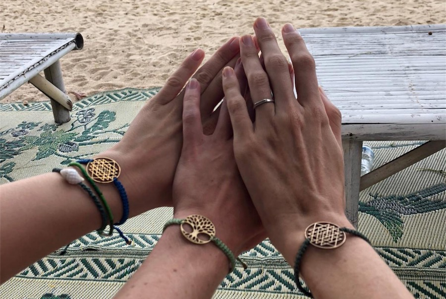 Three girls hold up their breath bracelets to the screens