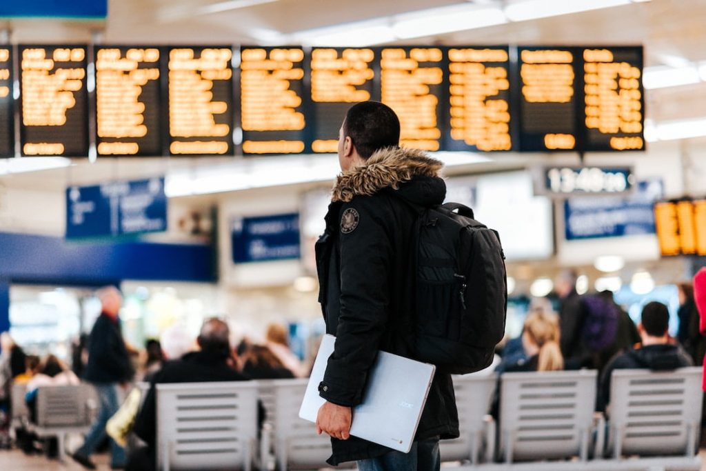 A man in a winter coat looks at an LED board of departure times in an airport