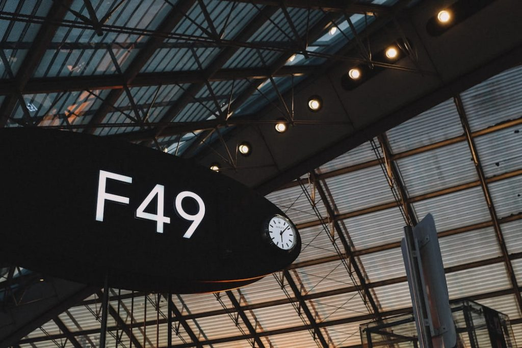 "An ovular airport gate that reads ""F49"" in an airport at sunrise"