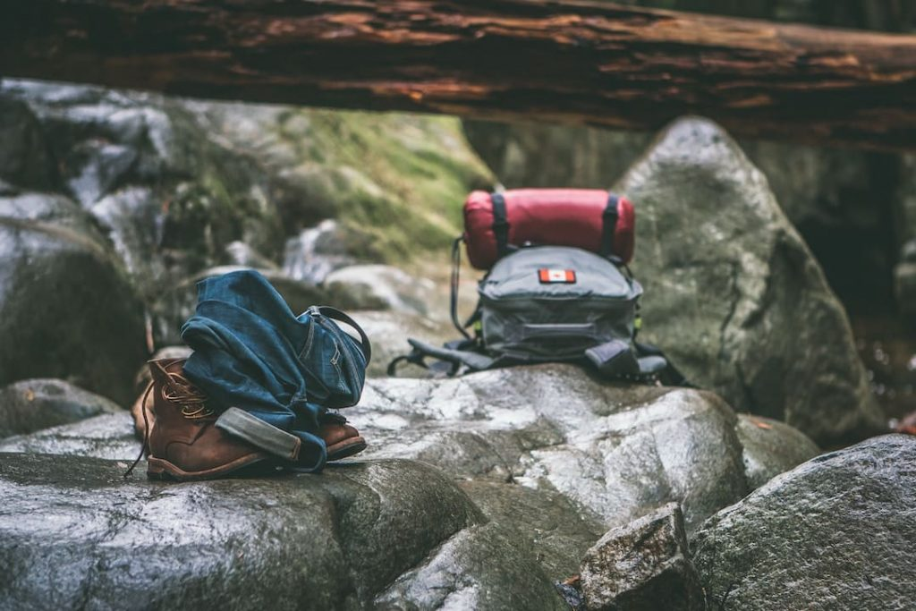 Two backpacks sitting on a rock outdoors