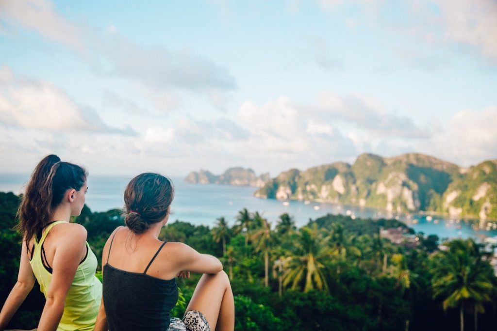 Two women sitting on a cliff, looking down at the Phi Phi Islands, Thailand
