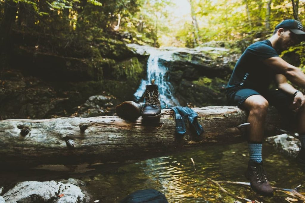 A man sitting on a log over running water, with a pair of hiking boots beside him