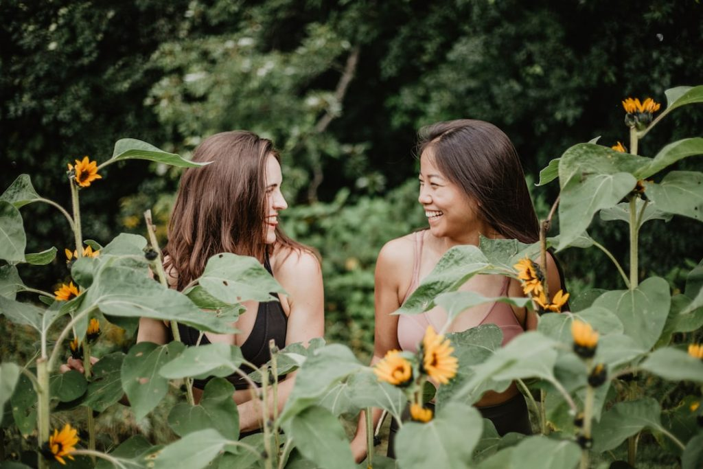 Two girls sit laughing together in nature surrounded by sunflowers