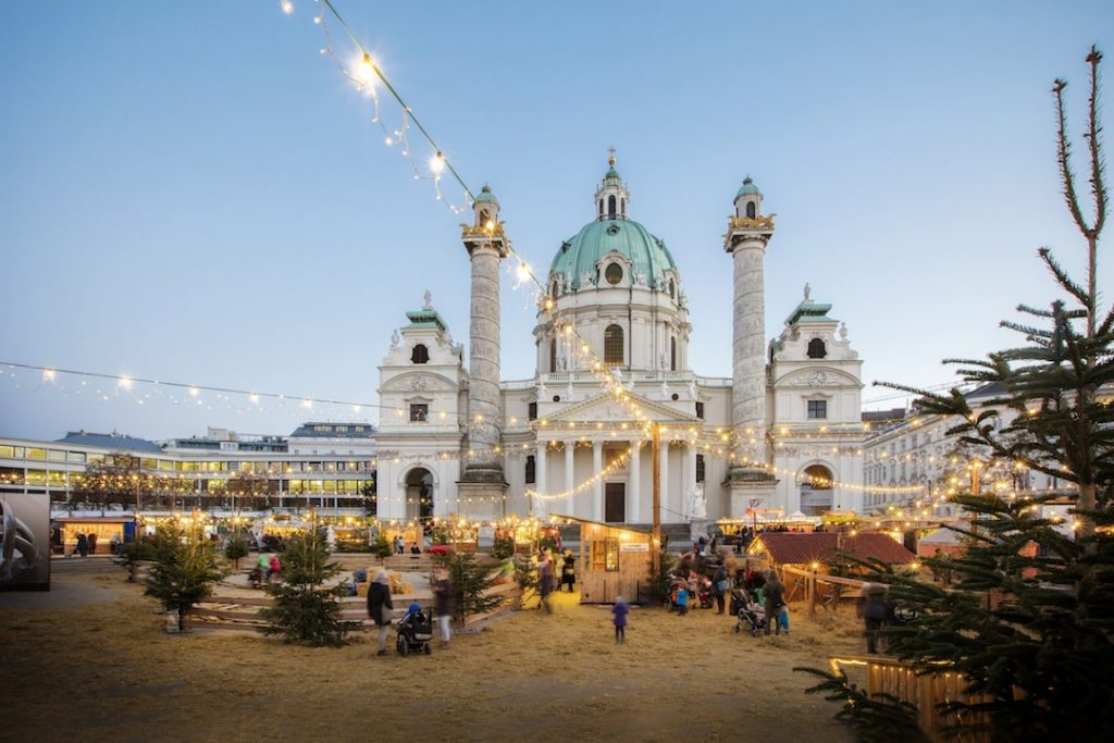 Christmas market with twinkling lights in front of a palace in Vienna