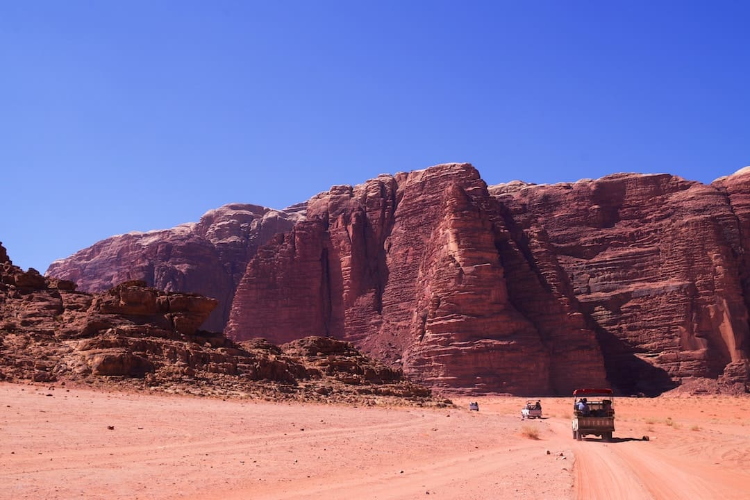 A series of vehicles driving towards a moutain in Wadi Rum, Jordan