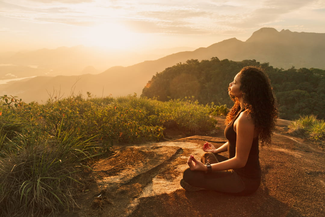 A woman sits cross-legged on a mountain at sunrise, facing the sun with her eyes closed