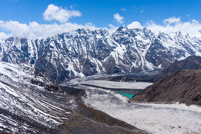a turquoise waterbody sits in a valley of the Manaslu Circuit