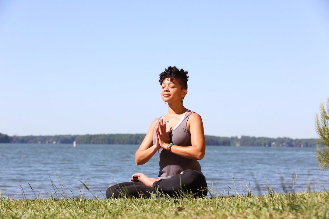 a woman sits in lotus pose on grass above a body of water