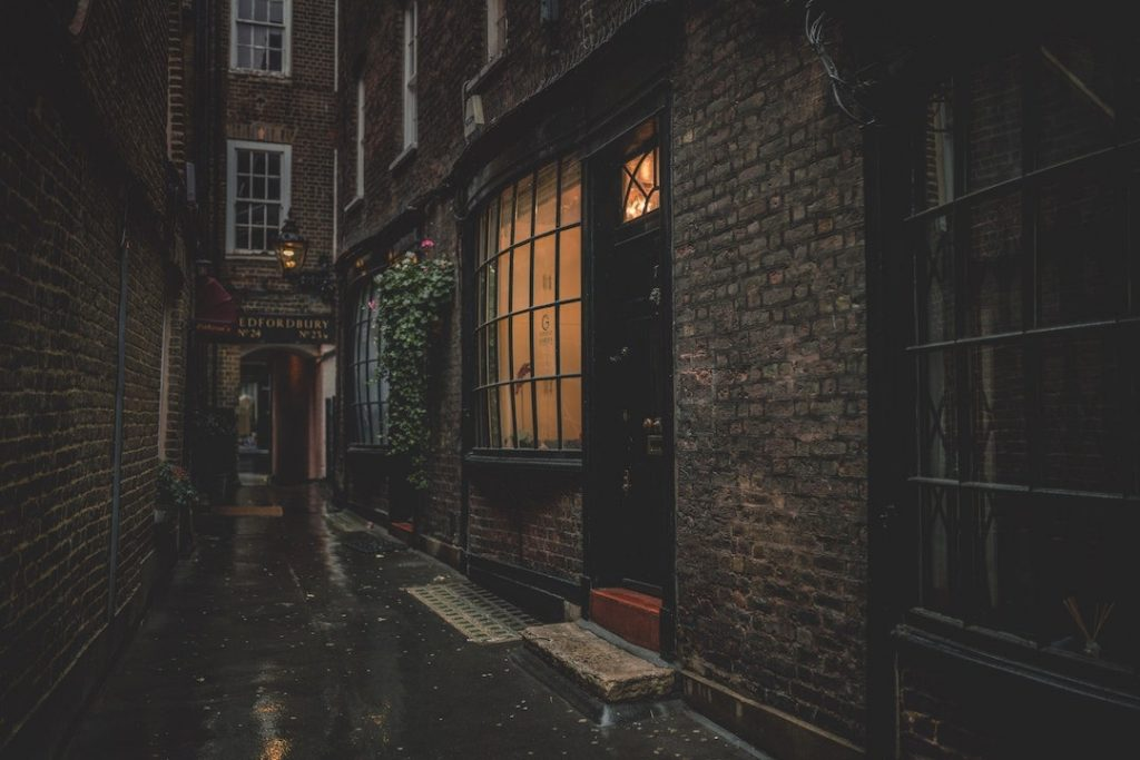 a dark alley in London with a light on in one window