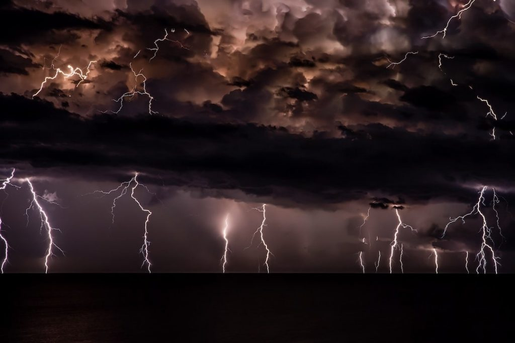 several bolts of lightning cracking into the ocean on a dark, gloomy night