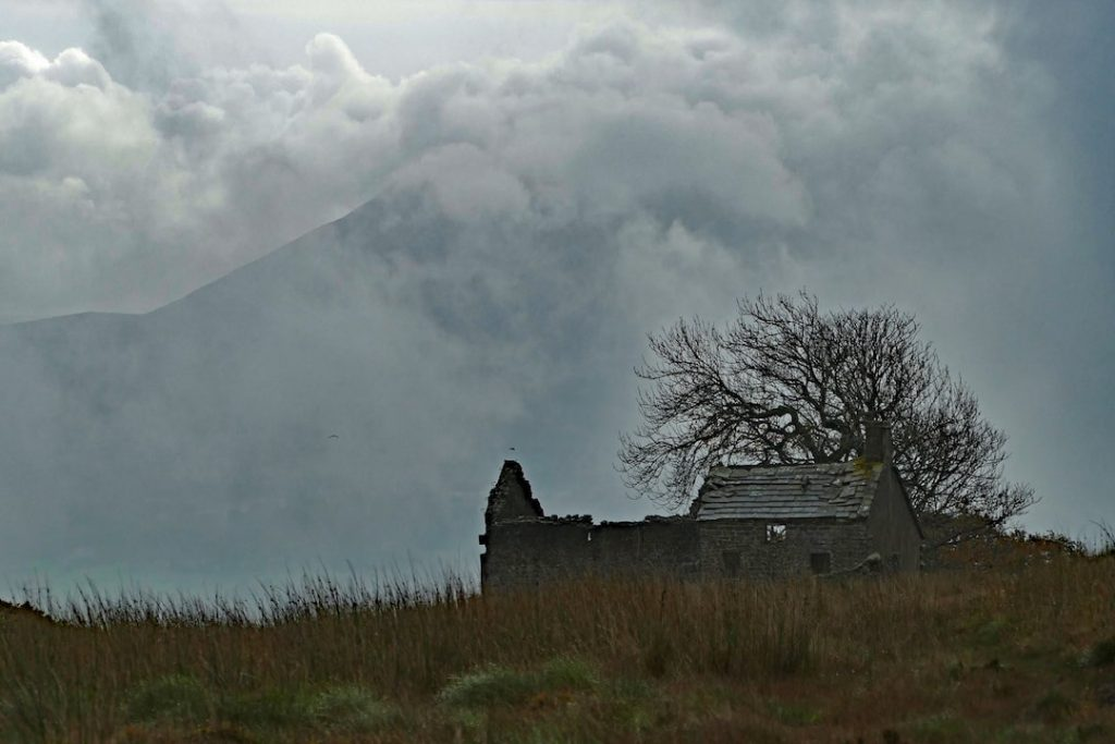 a ruin of an hold house in front of a leafless tree and a large hill on a foggy morning