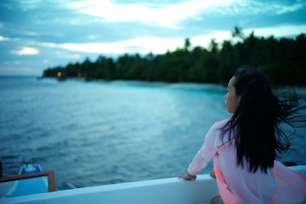 A girl on a boat faces the ocean in the Maldives