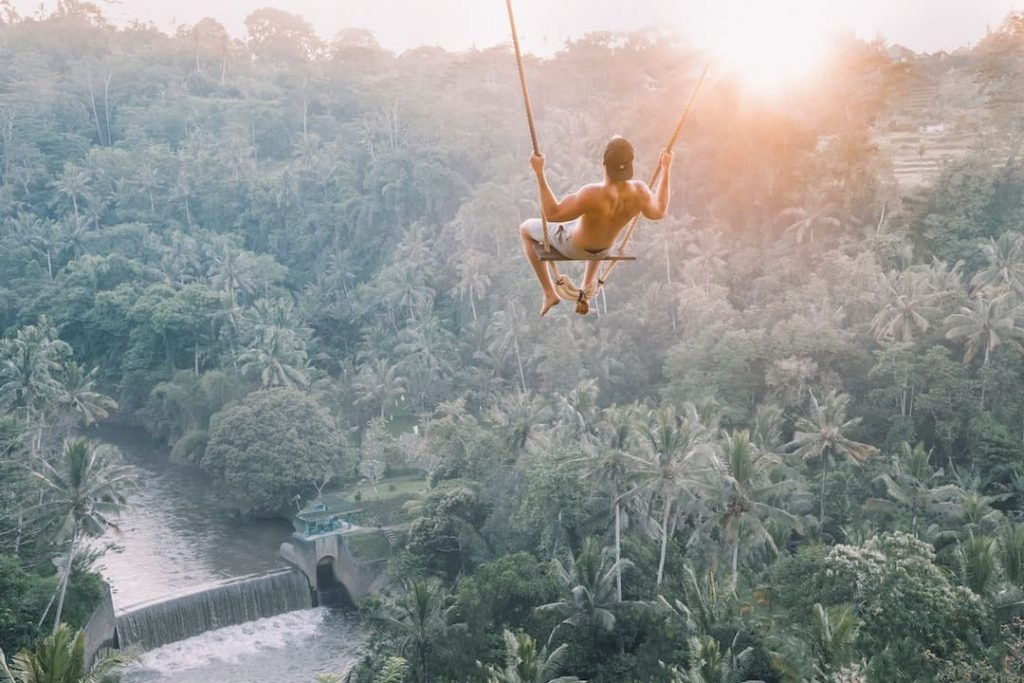 A man on a swing above the forest in Bali