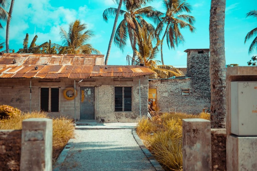 an abandoned house with a red roof on a sunny day in the Maldives