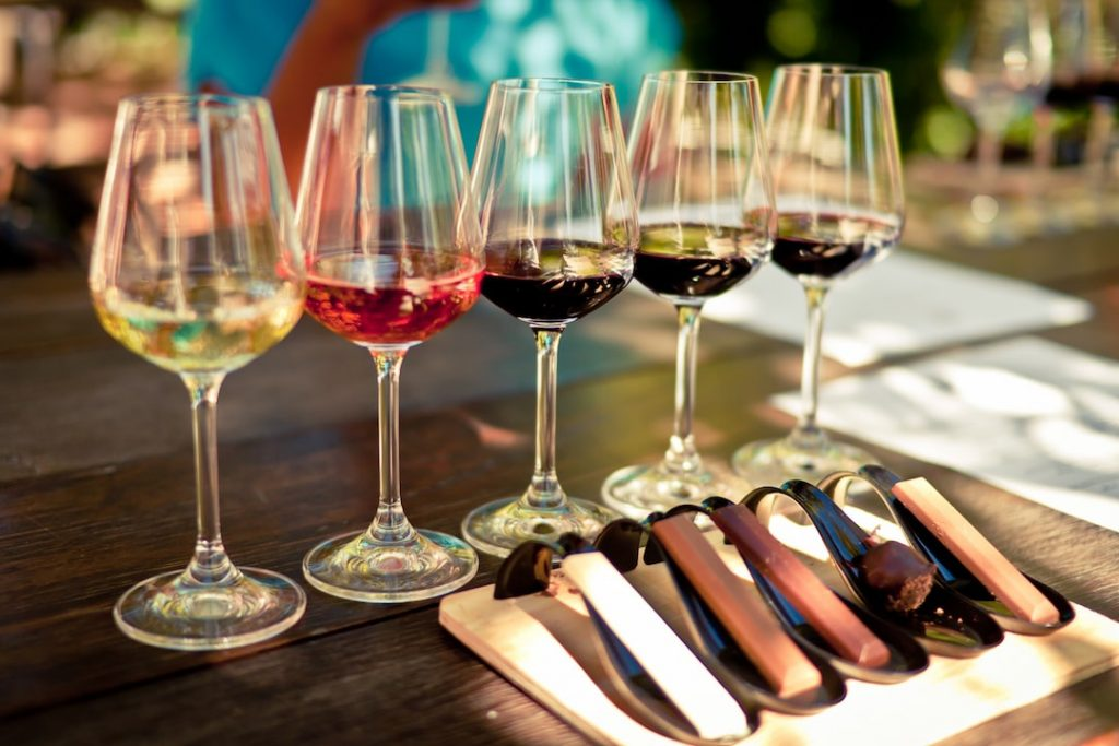 five glasses of wine, ranging from white to red, lined up for a tasting