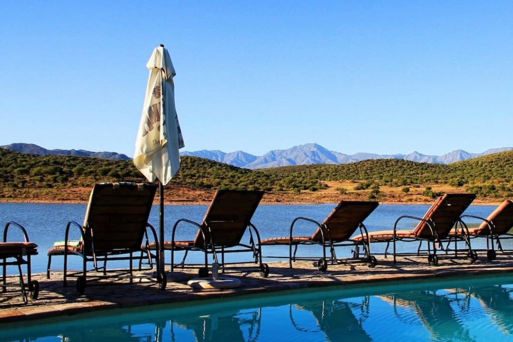 five deck chairs sitting by a pool with a body of water and mountain rage in the background in Klein Karoo, South Africa