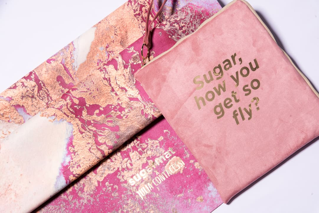 "a close-up of a marbled pink yoga mat beside a travel pouch that reads ""Sugar, how you get so fly?"""