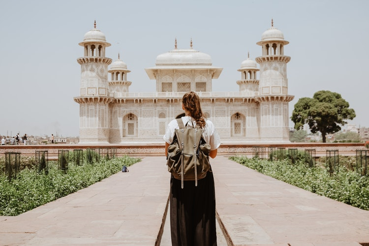 a girl with a back pack stands in front of a Tomb of I'timād-ud-Daulah in Agra India