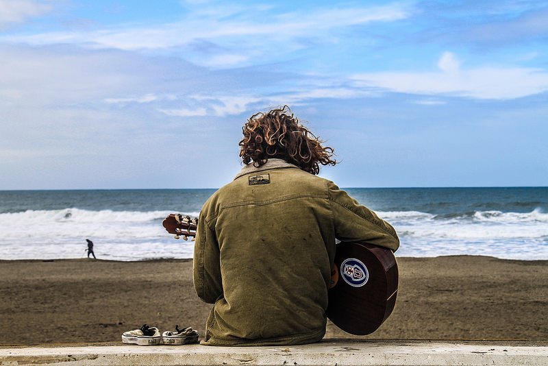 Man with his back to us plays the guitar on the beach