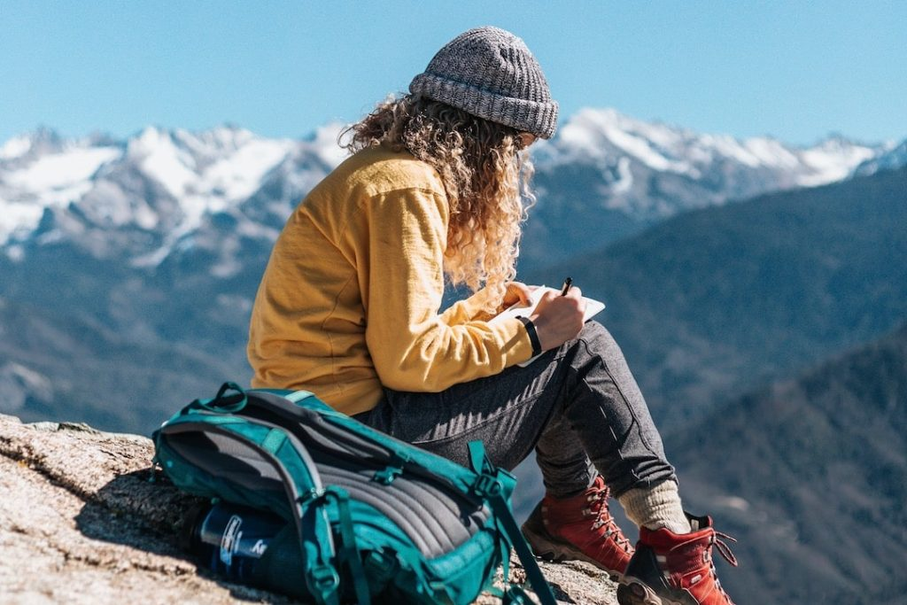 A girl sits on a rock with the mountains in the background writing in her journal