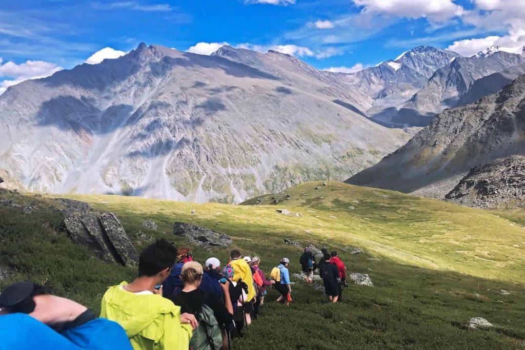 A line of people walking through a mountain range