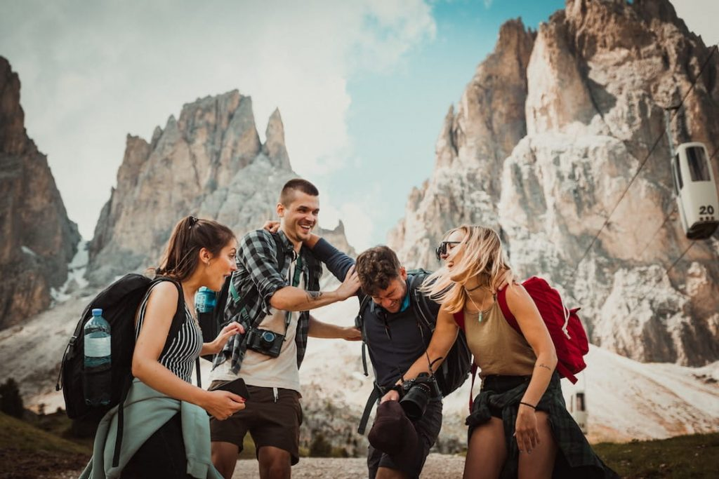 A group of four people stand in front of a rockface and laugh with each other